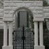 重厚な石造のアーチに組み込まれたクラッシクなデザインの重厚な門扉①