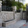 石造の塀の合わされたロートアイアンのフェンス