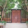庭園風の空間のアプローチにあるロートアイアンを組み込んだ木製扉